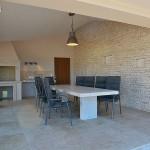 Außenküche mit Holzgrill, Doppelherdplatte und Waschbecken sowie gemütlichem Sitzbereich